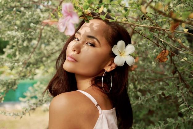 Schoonheidsportret van gelukkig aziatisch meisje met het mooie exotische gezicht stellen in tuin.