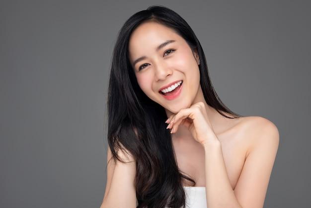 Schoonheidsportret van gelukkige mooie aasian-vrouw op grijze achtergrond