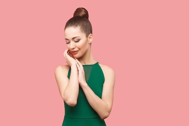Schoonheidsportret van gelukkige mooie jonge vrouw met knotkapsel en make-up in groene jurk die met gesloten ogen staat, haar gezicht aanraakt en glimlacht. indoor studio opname, geïsoleerd op roze achtergrond.
