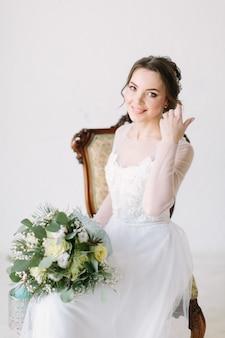 Schoonheidsportret van glimlachende bruid die de kleding van het manierhuwelijk met de samenstelling en het kapsel van de luxeverrukking dragen