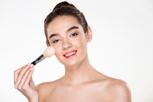 Schoonheidsportret van glimlachende halfnaakte vrouw met verse huid die make-up met zachte borstel en het kijken toepassen
