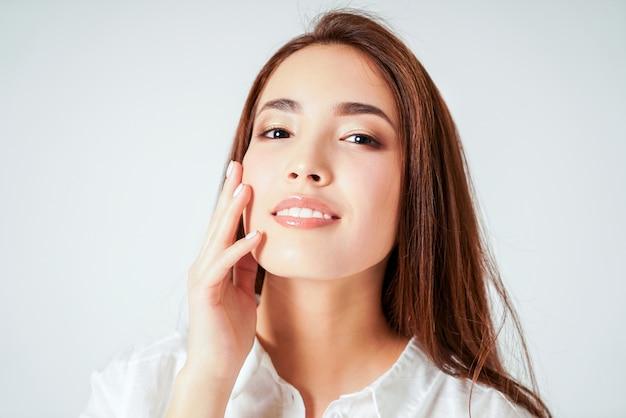 Schoonheidsportret van glimlachende sensuele aziatische jonge vrouw met schone verse huid in wit overhemd