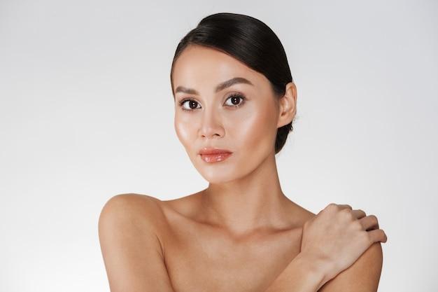 Schoonheidsportret van halfnaakte vrouw die op camera kijken en wat betreft haar zachte schouder, die over wit wordt geïsoleerd