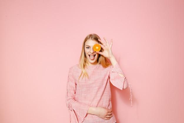 Schoonheidsportret van het gezonde aantrekkelijke vrouw stellen met gele mandarin die over roze achtergrond wordt geïsoleerd.