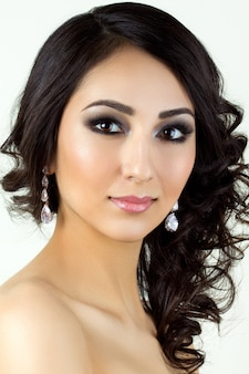 Schoonheidsportret van jonge brunettete vrouw met oorringen