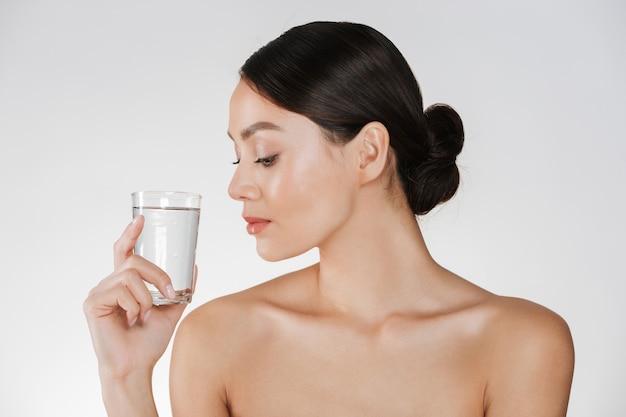 Schoonheidsportret van jonge gelukkige vrouw met haar in broodje die transparant glas van nog water bekijken die ter beschikking houden, dat over wit wordt geïsoleerd