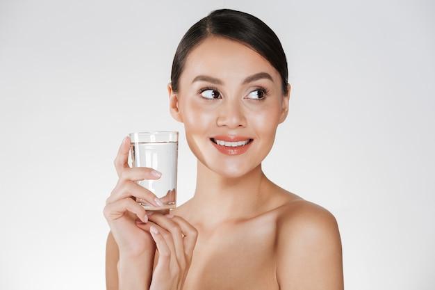 Schoonheidsportret van jonge gelukkige vrouw met haar in broodje het drinken nog water van transparant glas, dat over wit wordt geïsoleerd