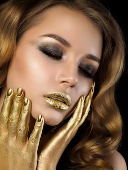 Schoonheidsportret van jonge vrouw met gouden huidmake-up over zwart