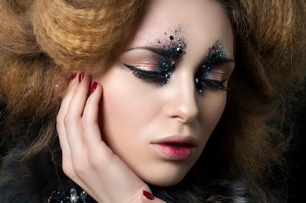 Schoonheidsportret van jonge vrouw met maniermake-up met strass steentjes wat betreft haar gezicht ... carnaval of partijmake-up