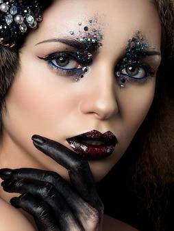Schoonheidsportret van jonge vrouw met maniermake-up met strass steentjes. zwarte hand en donkerrode lippen.