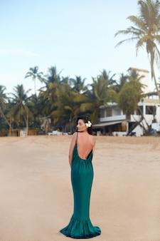 Schoonheidsportret van lachende vrouw in groene jurk aan zee. gelukkige mooie vrouw die aan de kust staat en wegkijkt.