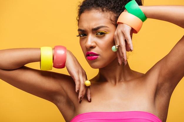 Schoonheidsportret van mooie afro amerikaanse vrouw met kleurrijke schoonheidsmiddelen en juwelen op handen die met zinvolle blik stellen die, over gele muur wordt geïsoleerd
