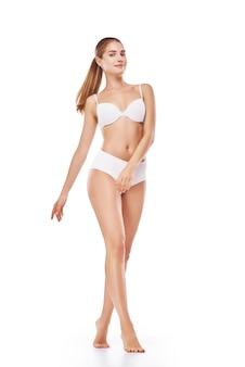 Schoonheidsportret van mooie jonge vrouw die in ondergoed staat