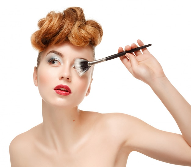 Schoonheidsportret van mooie vrouw met borstel voor make-up