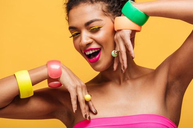 Schoonheidsportret van prachtige gemengd rasvrouw met maniermake-up en juwelen bij handen stellen geïsoleerd, over gele muur
