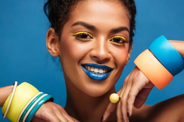 Schoonheidsportret van schitterende afro amerikaanse vrouw met maniermake-up en armbanden op handen die op camera met geïsoleerde glimlach kijken, over blauwe muur