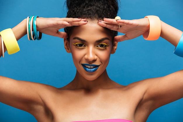 Schoonheidsportret van schitterende afro amerikaanse vrouw met maniermake-up en armbanden op handen die op camera met glimlach stellen geïsoleerd, over blauwe muur