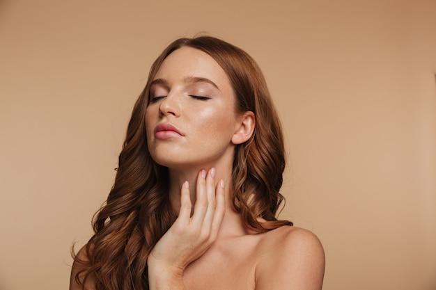 Schoonheidsportret van sensuele gembervrouw met het lange haar stellen met gesloten ogen