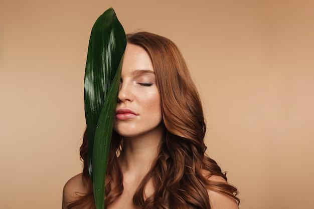 Schoonheidsportret van sensuele gembervrouw met het lange haar stellen met groen blad