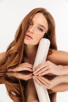 Schoonheidsportret van sensuele gembervrouw met lange haarzitting door de spiegellijst met fles lotion terwijl het kijken