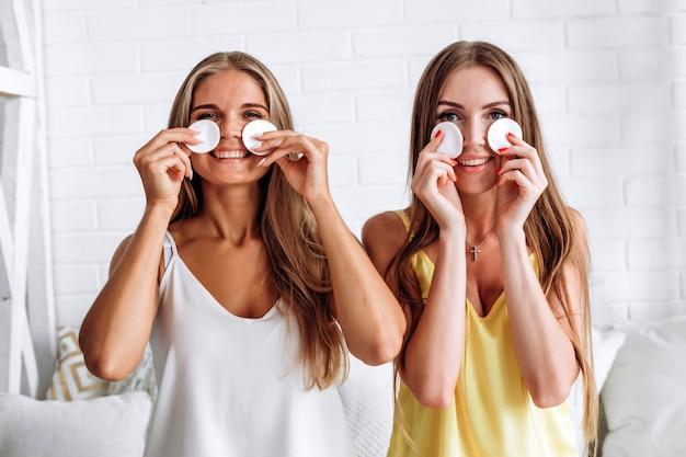 Schoonheidsportret van vrolijke vrouwen die gezichtssamenstelling met een katoenen stootkussen verwijderen