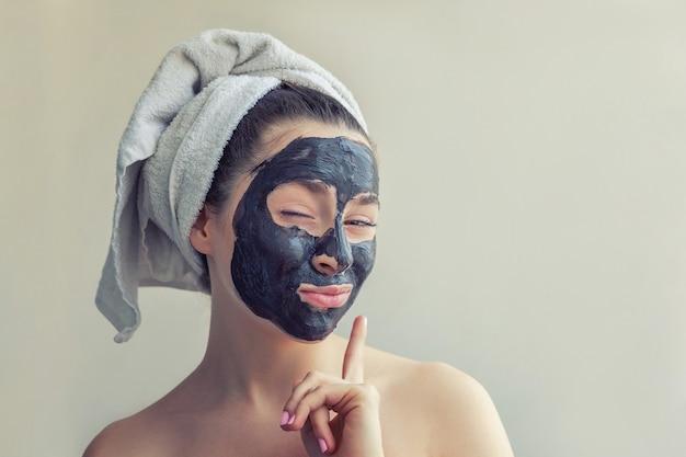 Schoonheidsportret van vrouw in handdoek op hoofd die zwart voedend masker op gezicht toepassen, witte geïsoleerde achtergrond. huidverzorging reiniging eco organische cosmetische spa relax concept