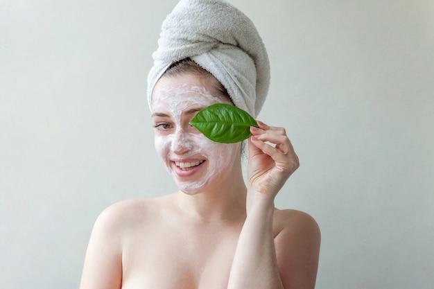 Schoonheidsportret van vrouw in handdoek op hoofd met wit voedend masker of room op gezicht en groen blad in hand, witte geïsoleerde achtergrond.
