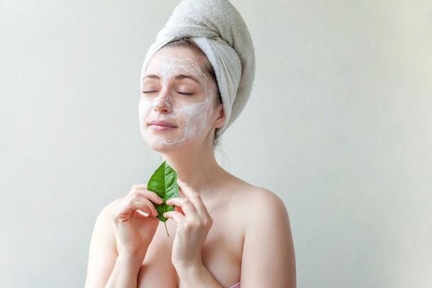 Schoonheidsportret van vrouw in handdoek op hoofd met wit voedend masker of room op gezicht en groen in hand blad