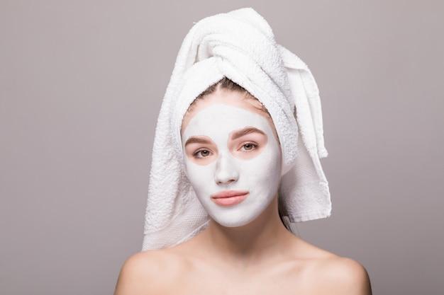 Schoonheidsportret van vrouw in handdoek op hoofd met wit voedend masker of room op gezicht, witte geïsoleerde muur. huidverzorging reinigende eco organische cosmetische spa ontspannen concept