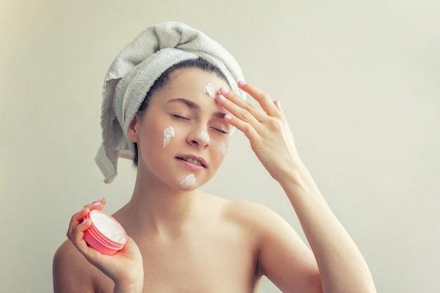 Schoonheidsportret van vrouw in handdoek op hoofd met wit voedend masker of room op gezicht, witte geïsoleerde muur