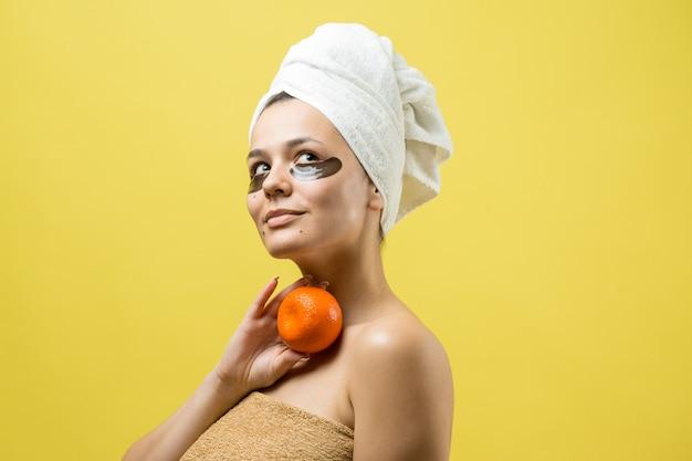 Schoonheidsportret van vrouw in witte handdoek op hoofd met gouden voedend masker op gezicht