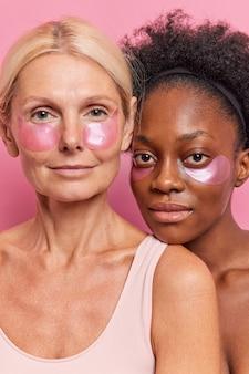 Schoonheidsportret van vrouwen van gemengd ras die hydrogelpleisters aanbrengen onder de ogen staan dicht bij elkaar
