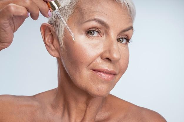 Schoonheidsprocedure. close-up van een schattige vrouw die haar glimlach laat zien terwijl ze voor haar huid zorgt
