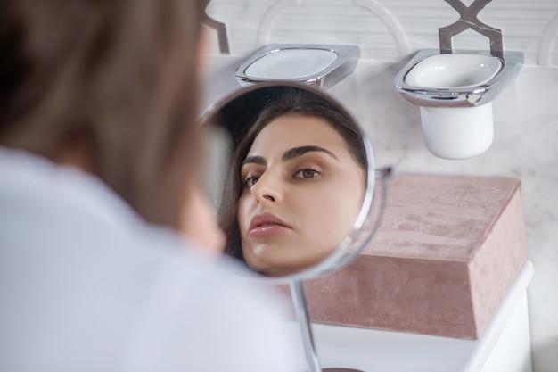Schoonheidsprocedures. een mooie vrouw die naar de kleine spiegel kijkt