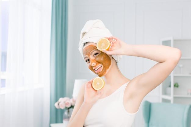 Schoonheidsprocedures huidverzorging concept. jonge vrouw met bruin gezichtsmasker van modderklei op haar gezicht in badkamers, met witte handdoek op hoofd, die citroenhelft houden