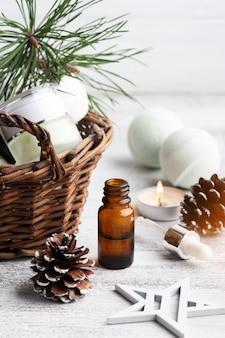 Schoonheidsproduct in mand in christmas spa-samenstelling met pijnboomtakken en etherische olie, aangestoken kaars