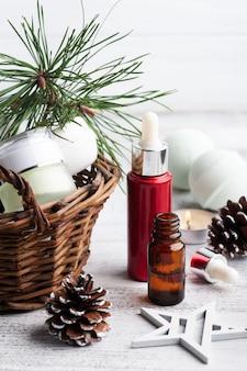 Schoonheidsproduct in mand in christmas spa-samenstelling met pijnboomtakken en sterren, aangestoken kaars