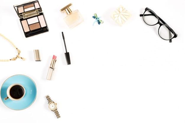 Schoonheidsproducten, koffiekopje en stijlvolle vrouwelijke accessoires op witte achtergrond