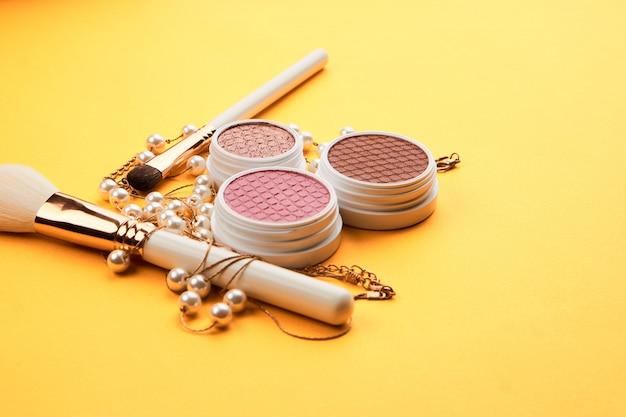 Schoonheidsproducten op een gele tafel, cosmetica en sieraden