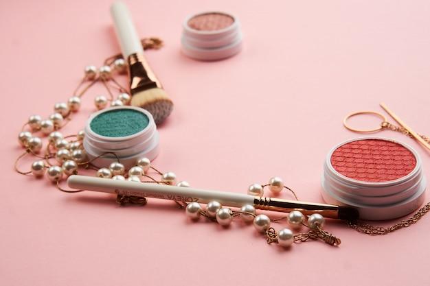 Schoonheidsproducten op een roze tafel, cosmetica en sieraden