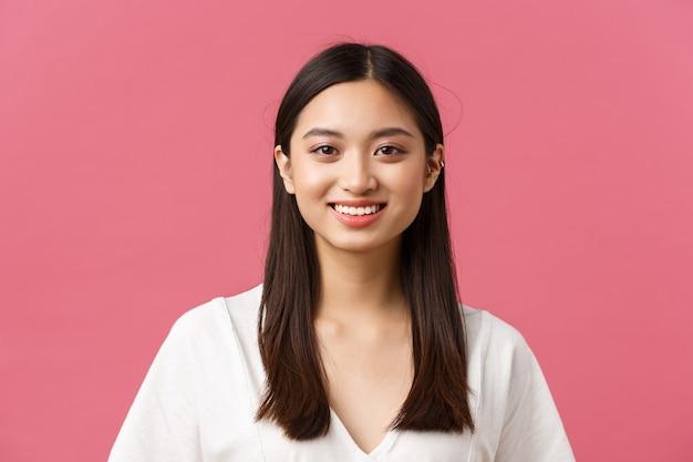 Schoonheidsproducten reclame, haarverzorging en damesmode concept. close-up van schattig romantisch dom aziatisch meisje met medium donker kapsel, glimlachend witte tanden met gelukkige uitdrukking, roze achtergrond.