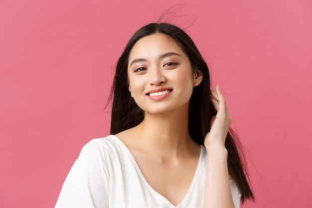 Schoonheidsproducten reclame, haarverzorging en damesmode concept. close-up van sensuele mooie koreaanse vrouw die breed lacht met witte tanden, zachtjes aan het kapsel aanraakt, op een roze achtergrond staat.