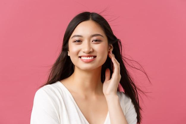 Schoonheidssalon, haarverzorging en huidverzorgingsproducten advertentie concept. close-up van mooie jonge aziatische vrouw die lacht als wind zachtjes waait op kapsel, staande roze achtergrond.