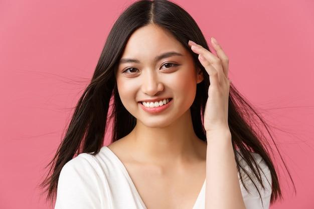 Schoonheidssalon, haarverzorging en huidverzorgingsproducten advertentie concept. schitterende aziatische vrouw 20s, zachtjes aanraken van haar en lachend met verlegen romantische uitdrukking, staande roze achtergrond