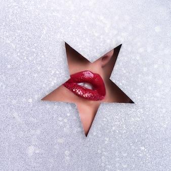 Schoonheidssalon reclamebanner met kopie ruimte. weergave van heldere lippen met glitters door gat in zilver papier achtergrond.