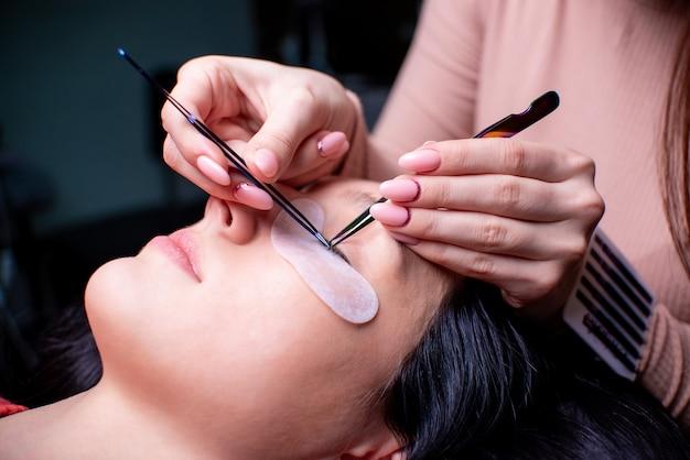 Schoonheidssalon, wimper extensie procedure close-up. mooie vrouw met lang haar