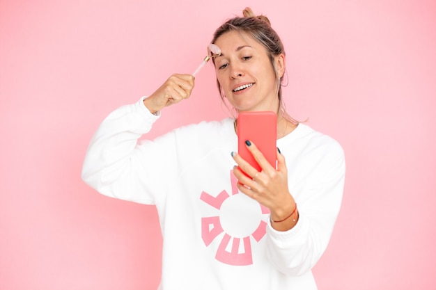 Schoonheidssalonspecialist lacht terwijl hij via smartphone met de klant communiceert en legt de principes van guasha-massage uit. klantgerichte benadering, stockfoto op roze achtergrond