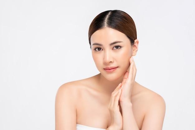Schoonheidsschot van jeugdige heldere huid vrij aziatische vrouw met hand wat betreft gezicht