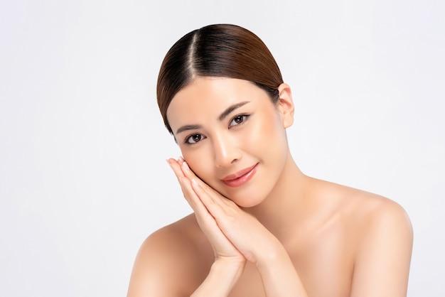 Schoonheidsschot van jeugdige heldere huid vrij aziatische vrouw met handen wat betreft gezicht