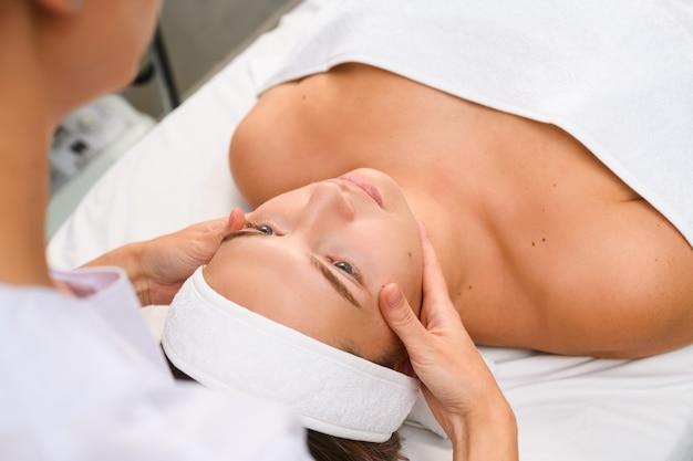 Schoonheidsspecialist aanraking gezicht en nek van jonge patiënt liggend op de bank